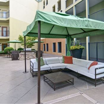 Sitting Area has Orange Pillows and Green Shades over White Outdoor Furniture