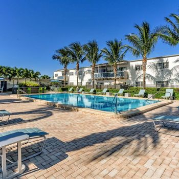 The Dunes Indian Harbour Beach, Florida sparkling swimming pool surrounded by palm trees and lounge seating