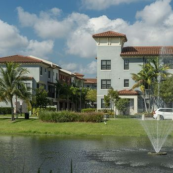 Building exterior next to a lake surrounded by lush greenery and palm trees.