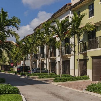 Building exterior surrounded by lush greenery and palm trees.