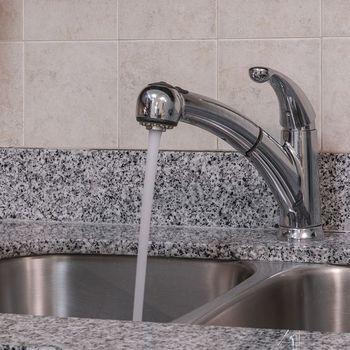 Faucet fixture and granite countertops.