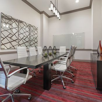 Community business center with a long table and comfortable chairs.