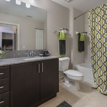Bathroom with granite countertops and framed mirror.